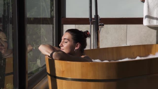 lüks banyoda sıcak banyo alan kadın - kendini şımartmak stok videoları ve detay görüntü çekimi