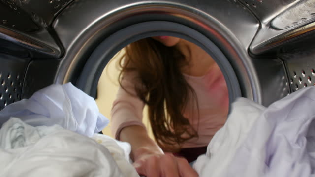 Woman Taking Laundry Out Of Washing Machine video
