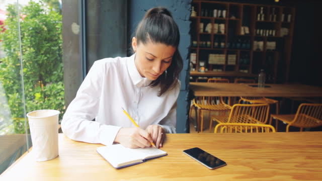Woman taking notes in the coffee shop. video
