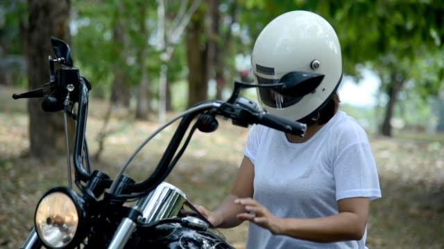 vídeos de stock e filmes b-roll de woman taking off motorcycle helmet. - helmet motorbike