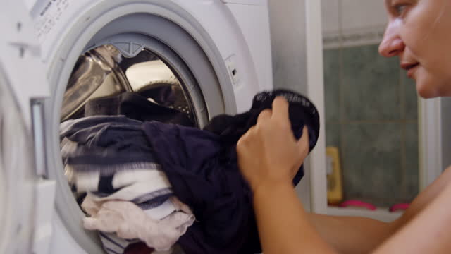 Woman taking out clothes from the washing machine