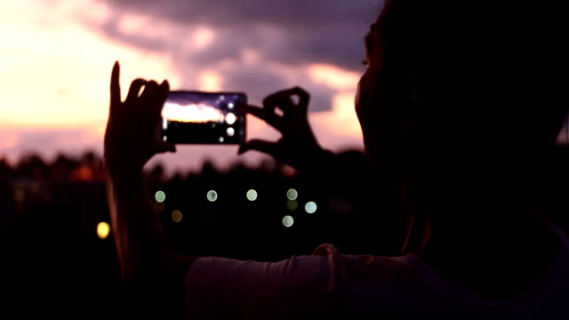 Woman taking photo of sunset sky