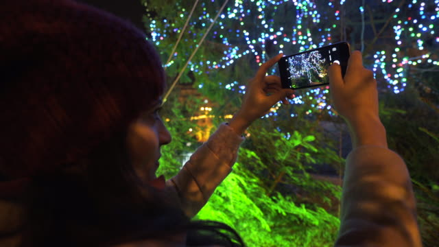 Woman taking photos in front of the Christmas tree. video