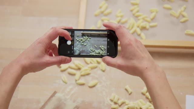 vidéos et rushes de femme prenant des photos des pâtes avec son téléphone intelligent. - photophone