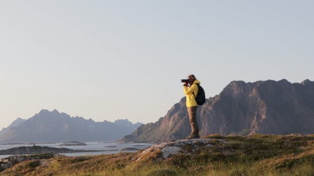 Woman taking pictures of a Norwegian landscape from a hill with a DSLR camera.