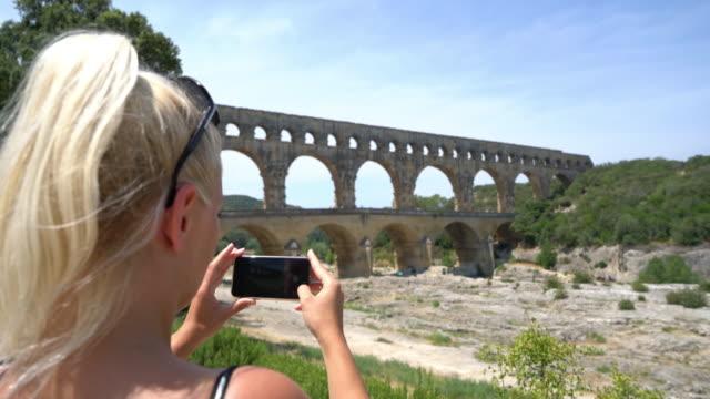 stockvideo's en b-roll-footage met ws vrouw foto's maken van de pont du gard - pont du gard