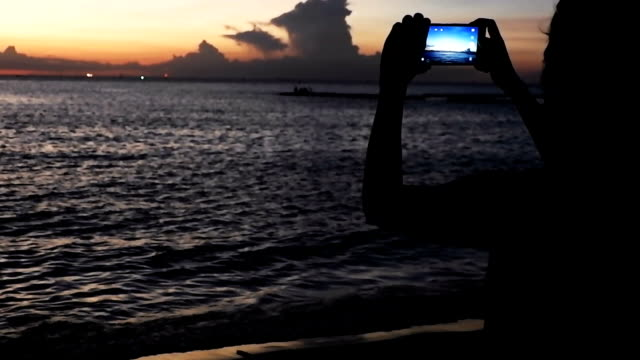 Woman Taking Pictures with her Smartphone at Sunset on the Beach near the Sea on Vacation. video