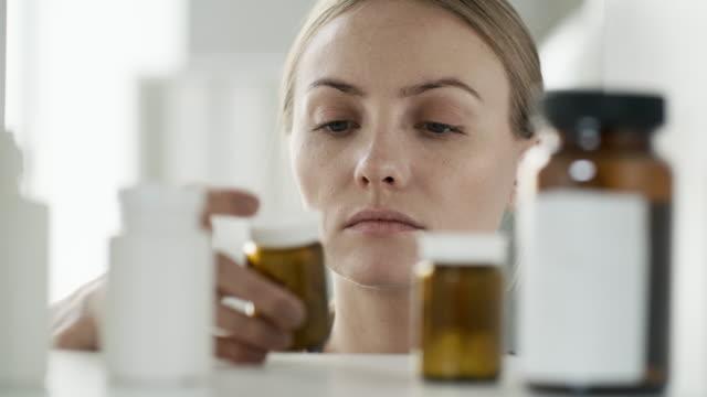 Bидео Woman Taking Pills from Medicine Cabinet