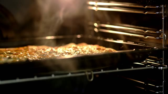 ds woman taking pizza out of the oven - piec przygotowywać jedzenie filmów i materiałów b-roll