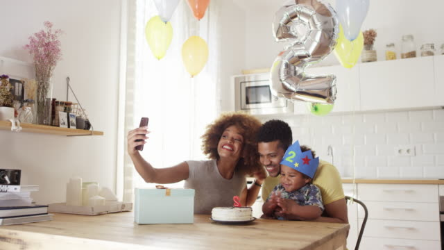 Woman taking selfie with family during birthday