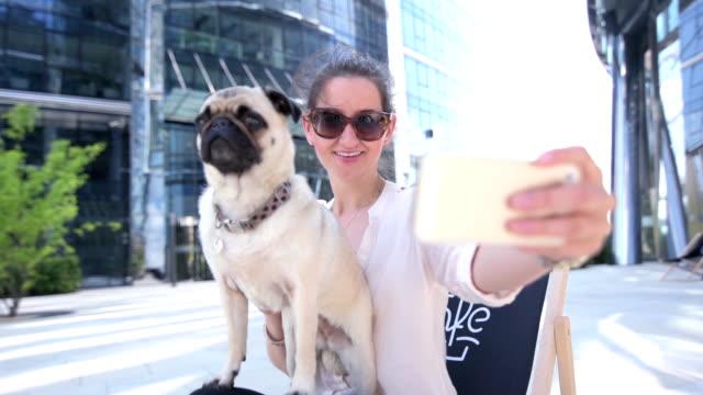 vídeos de stock e filmes b-roll de mulher a tirar selfie com seu cão em uma rua café - fotografar