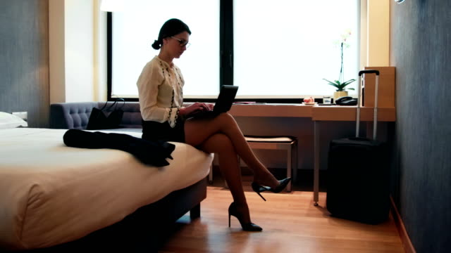 Vrouw nemen van schoenen uit zakenvrouw In hotelkamer tijdens reis video
