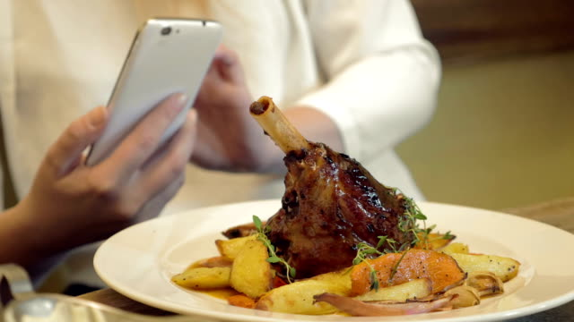Woman taking shot of delicious restaurant dish video