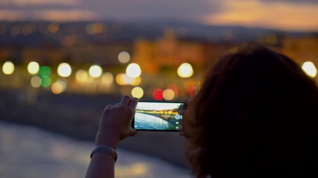 Woman taking shots of evening city using smartphone. Nice, France. 4K, UHD