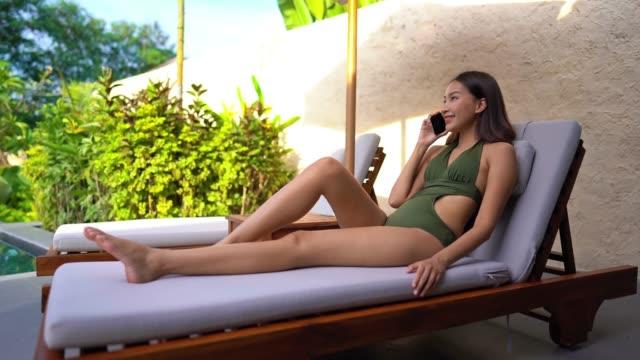 Woman talking mobile phone around swimming pool