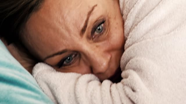 Woman talking on cell phone in bed