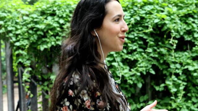 kadın bitkiler tarafından telefon kullanarak kulaklık üzerinde söz - kulak i̇çi kulaklık stok videoları ve detay görüntü çekimi
