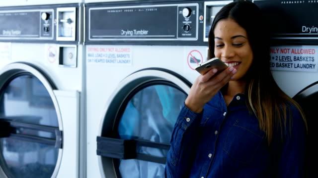 vidéos et rushes de femme parlant sur téléphone mobile à la laverie automatique 4k - 18 19 ans