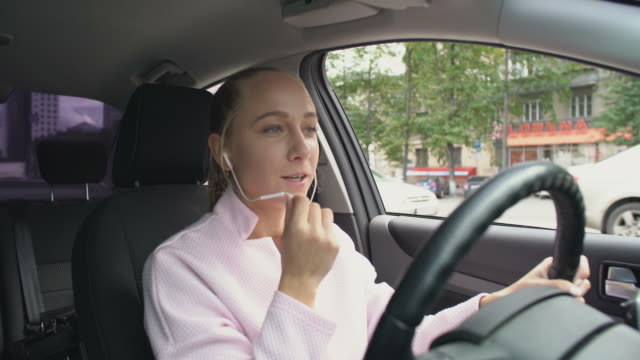 Woman Talking on Phone in Car Shot from inside of car of cheerful young stylish woman driving car and talking on phone with hands-free device bluetooth stock videos & royalty-free footage