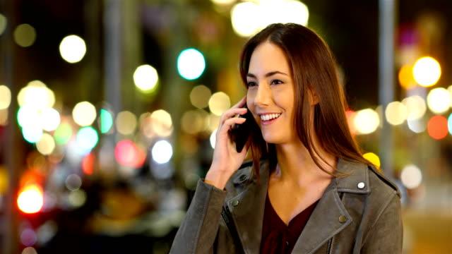 woman talking on phone in the night in the street - ear talking video stock e b–roll
