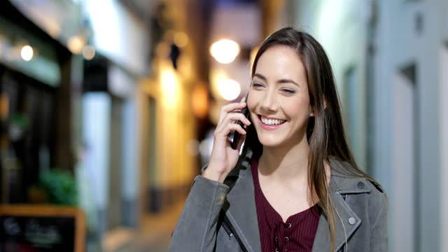 夜に歩いて電話で話している女性 - 電話を使う点の映像素材/bロール