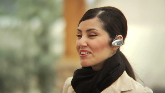 Woman talking on phone with earpiece video