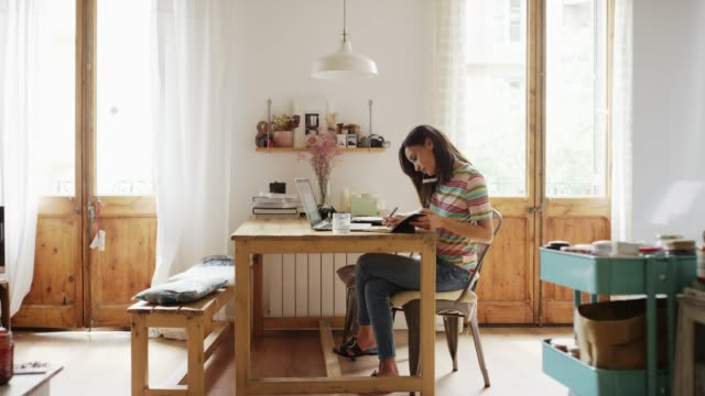 Woman talking on smart phone while working at home