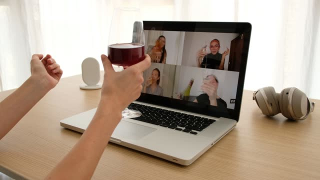 Woman talking on video chat with friends Crop female sitting with glass of wine at table and making video call via laptop with girlfriends while having remote party during coronavirus outbreak girlfriend stock videos & royalty-free footage