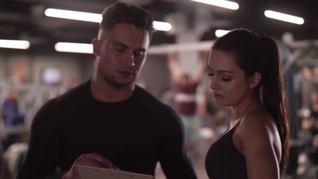 stockvideo's en b-roll-footage met vrouw praten coach bij healthclub - fitnessleraar