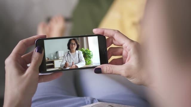 vídeos de stock, filmes e b-roll de mulher que fala ao doutor através da chamada video do telefone esperto. consulta médica on-line - telemedicina