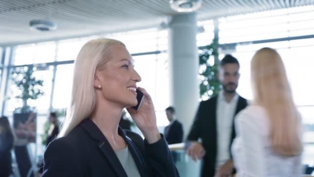 ds kvinna prata med hennes familj på telefonen medan du går genom businesslounge på flygplatsen - kvinna tillfreds bildbanksvideor och videomaterial från bakom kulisserna