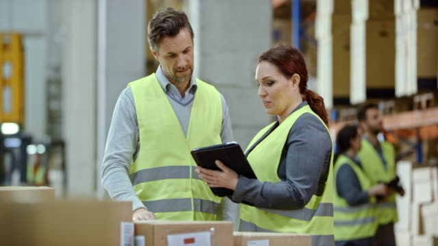 Woman talking to her male coworker in the warehouse while holding a tablet video