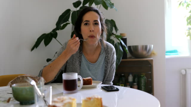 Woman talking while having breakfast at home