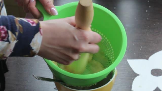 vídeos de stock, filmes e b-roll de uma mulher bate maçãs fervidas no applesauce. usa coador e rolo de pino. - feito em casa