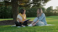 istock Woman teacher and girl student teenager sitting on the grass in park talking, testing, learning 1279279538