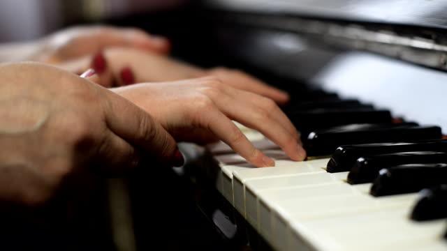 Mulher ensina as crianças para brincar o piano. - vídeo