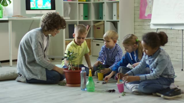 Woman Teaching Kids How to Repot Plant video