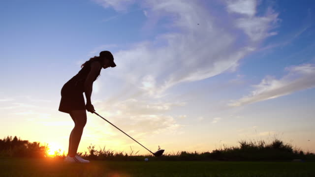 Woman tees off at dawn video