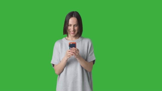 vídeos de stock, filmes e b-roll de mensagem de texto da mulher no telefone móvel sobre o fundo verde - fundo verde