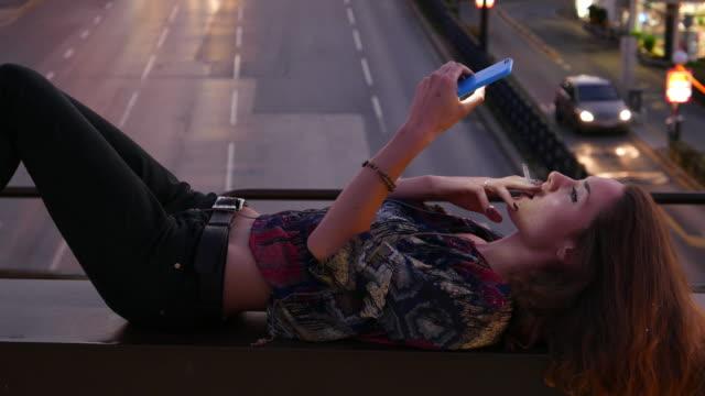 woman texting at the bridge - sigaretta video stock e b–roll