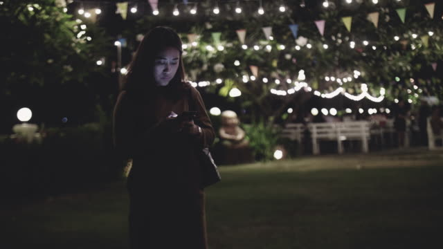 Woman texting on mobile phone in the city at night