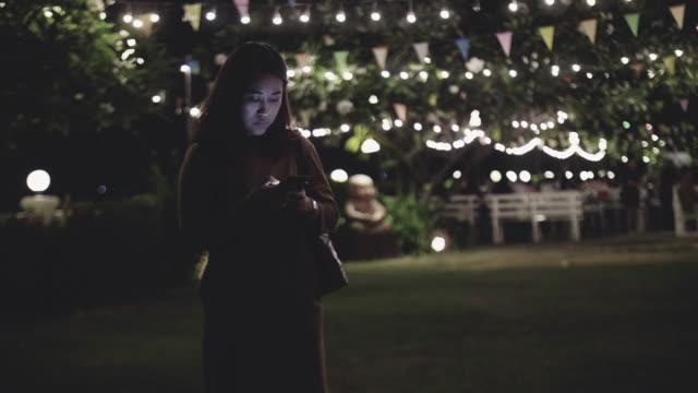 frau sms auf dem handy in die stadt bei nacht - online dating stock-videos und b-roll-filmmaterial