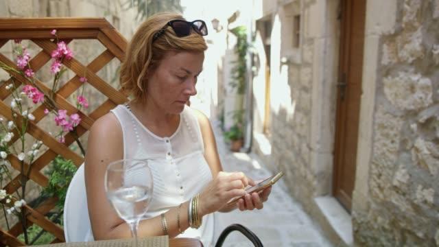 ms-woman sms mit ihrem smartphone im café in gasse - einzelne frau über 30 stock-videos und b-roll-filmmaterial