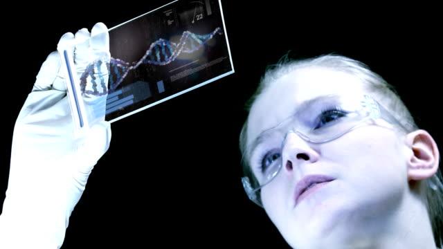 frau ist die wissenschaftler analysieren struktur dna. - wissenschaftlerin stock-videos und b-roll-filmmaterial