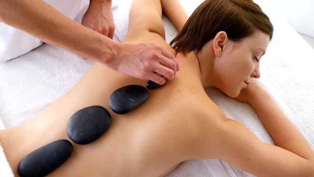 woman therapist putting hot stones - terapia lastone filmów i materiałów b-roll