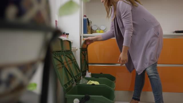 vídeos de stock e filmes b-roll de woman throwing away trash and taking it out - economia circular