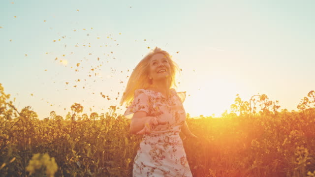 slo mo woman throwing canola crops up in the air - trentenne video stock e b–roll