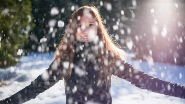 Woman throwing snow in the air video