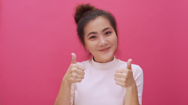 Woman thumb up look at camera isolated pink background 4k