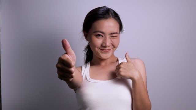 Woman thumb up look at camera isolated white background 4k